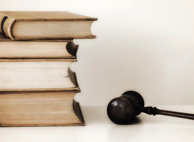 Judges gavel beside stacked law books --- Image by © Tetra Images/Corbis